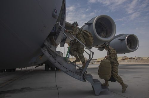 Aircrew assigned to Al Udeid Air Base, Qatar, carry their gear into a C-17 Globemaster III assigned to Joint Base Charleston, South Carolina, April 27, 2021, at Al Udeid AB. U.S. Air Force C-17s and other mobility aircraft around the U.S. Air Forces Central theater are assisting with the safe and orderly drawdown operations from Afghanistan
