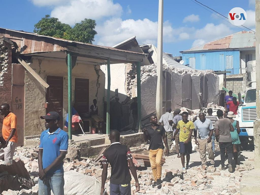 Haitians walk down the street, looking at the rubble left by the August 14 earthquake.