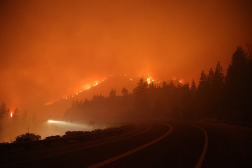 A mountain ridge is outlined in flames that are part of the Caldor Fire on August 29, 2021.