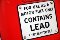 """Warning sign saying, """"For use as a motor fuel only. CONTAINS LEAD (Tetraethyl)""""."""