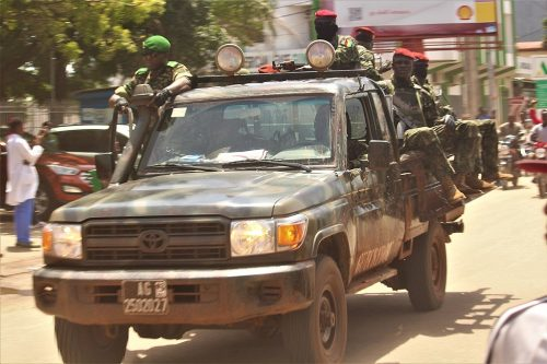 A truck full of soldiers wearing red berets rolls down the streets of Conakry after the 2021 coup in Guinea.