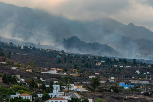 Smoke rises from a huge stretch of land burned by the volcanic eruption on La Palma.