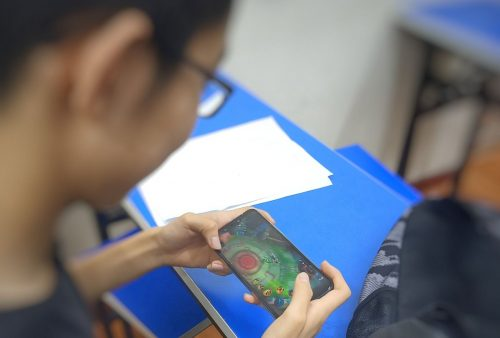 Student playing Wangzhe Rongyao video game on a smart phone.