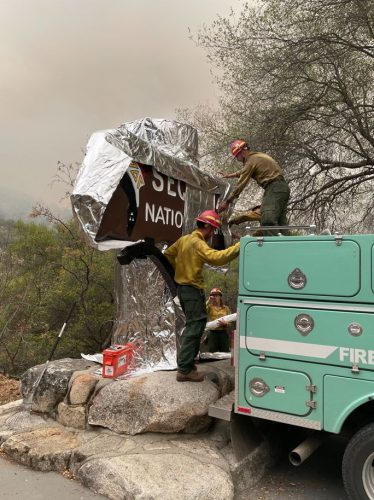 Firefighters prepare the historic Sequoia entrance sign.