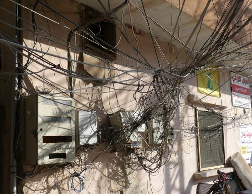 A muddle of power cables on a residential building with a yellow Hezbollah poster on the right in the Southern Lebanese city of Tyre/Sour.