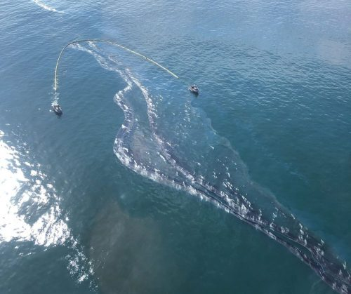 Aerial view showing Coast Guard ships laying a retaining boom during the oil spill off the coast of Orange county, California on October 3, 2021.
