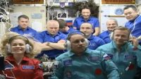 Yulia Peresild, Anton Shkaplerov, and Klim Shipenko (front row) seen on the ISS along with other members of the space station crew during a video meeting.